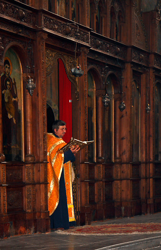 priest wearing orange vestments reading from prayer book emerging from altar; St. Dimitri Eastern Orthodox Church; 1901; Vidin; Bulgaria