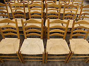 close up of old style chairs lined up in an church
