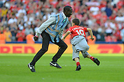 Young Liverpool pitch invader side steps security guard during the International Champions Cup between Liverpool FC and FC Barcelona at Wembley Stadium, London, England on 6 August 2016. Photo by Mark Davies.