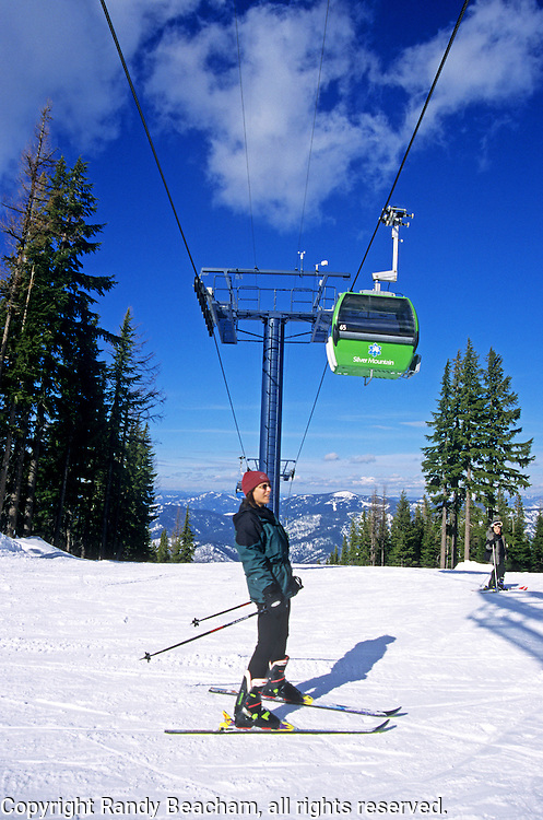 Woman skier and gondola at Silver Mountain Ski Resort. Near Kellog, north Idaho.