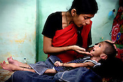 Tasleen, 26, the mother of Zubin, 3, a severely disabled girl, is soothing her suffering daughter inside their home in one of the water-affected colonies near the abandoned Union Carbide (now DOW Chemical) industrial complex in Bhopal, Madhya Pradesh, India, site of the infamous 1984 gas tragedy. The poisonous cloud that enveloped Bhopal left everlasting consequences that today continue to consume people's lives. Zubin has deceased.