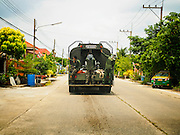 14 JULY 2015 - THAILAND:   A Thai army water truck drives through a residential development in Pathum Thani province near Bangkok. The drought that has crippled agriculture in central Thailand is now impacting residential areas near Bangkok. The Thai government is reporting that more than 250,000 homes in the provinces surrounding Bangkok have had their domestic water cut because the canals that supply water to local treatment plants were too low to feed the plants. Local government agencies and the Thai army are trucking water to impacted communities and homes. Roads in the area have started collapsing because of subsidence caused by the retreating waters. Central Thailand is contending with drought. By one estimate, about 80 percent of Thailand's agricultural land is in drought like conditions and farmers have been told to stop planting new acreage of rice, the area's principal cash crop.     PHOTO BY JACK KURTZ
