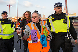 London, UK. 17th November, 2018. Police officers arrest Genny Scherer (c) and another woman after environmental campaigners from Extinction Rebellion blocked Blackfriars Bridge, one of five bridges blocked in central London, as part of a Rebellion Day event to highlight 'criminal inaction in the face of climate change catastrophe and ecological collapse' by the UK Government as part of a programme of civil disobedience during which scores of campaigners have been arrested.