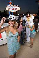 Portrait of young woman, two women with Elvis impersonator in background, Las Vegas, Nevada, USA