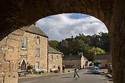 The A6306 road passing the Lord Crewe Arms Hotel in the Northumbrian village of Blanchland on 29th September 2017, in Blanchland, Northumberland, England. Blanchland is a village in Northumberland, England, on the County Durham boundary. The population of the Civil Parish at the 2011 census was 135. Blanchland was formed out of the medieval Blanchland Abbey property by Nathaniel Crew, 3rd Baron Crew, the Bishop of Durham, 1674-1722. It is a conservation village, largely built of stone from the remains of the 12th-century Abbey. It features picturesque houses, set against a backdrop of deep woods and open moors. Set beside the river in a wooded section of the Derwent valley, Blanchland is an attractive small village in the North Pennines Area of Outstanding Natural Beauty.