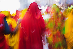A motion-blur of village women shopping together dressed in multi-colored saris, Pushkar camel fair,Rajasthan, India