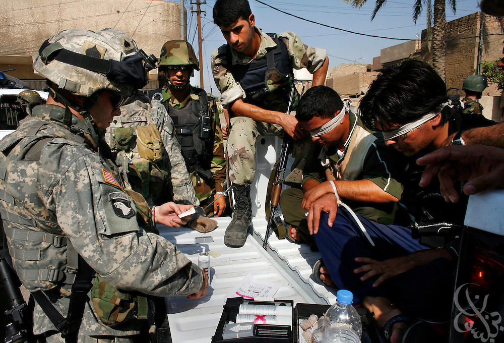 Iraqi National police watch as a U.S. Army 101st Airborne soldier tests Iraqi suspects for explosive residue during a joint security operation by Iraqi National police and U.S. Army in the Doura district of Baghdad, Iraq, on Tuesday, Aug. 8, 2006.