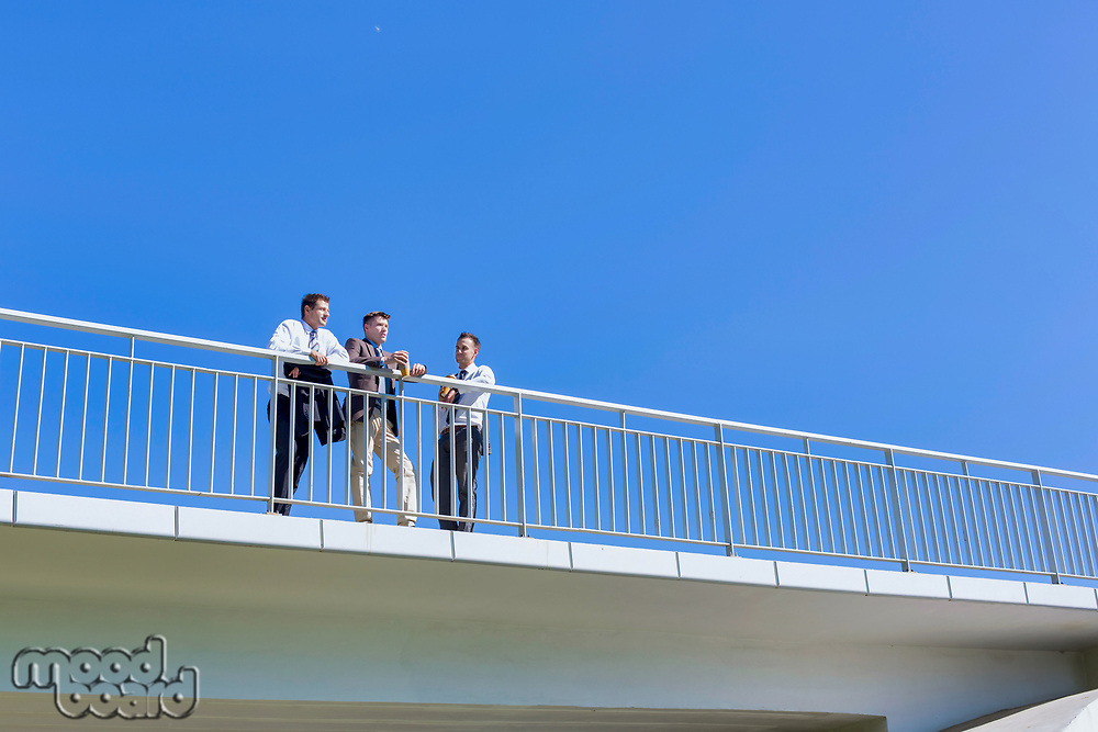 Portrait of mature thoughtful attractive businessman drinking coffee while standing on the bridge with colleagues