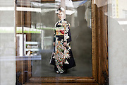 window reflection with image of young woman in kimono Display of local photo portrait studio in Japan