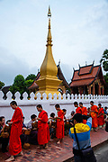 Monks and tourists particate in sai bat (morning alms giving), Luang Prabang, Laos.