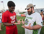 A member of the Waltrip High School football team talks with a player before the Wounded Warrior Amputee Football Team game against NFL Alumni, at Delmar Stadium, February 1, 2017.