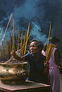 Lighting incense sticks and praying at the Thien Hai Temple in Saigon during Moon Festival.