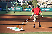 ANAHEIM, CA - AUGUST 18:  A groundskeeper rakes the infield dirt after pregame warmups at the Los Angeles Angels of Anaheim game against the Texas Rangers on August 18, 2011 at Angel Stadium in Anaheim, California. The Angels won the game 2-1. (Photo by Paul Spinelli/MLB Photos via Getty Images)