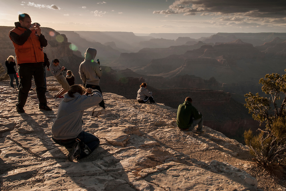 Tourists take in the sunset view of the Grand Canyon from the South Rim. Grand Canyon National Park, Arizona.