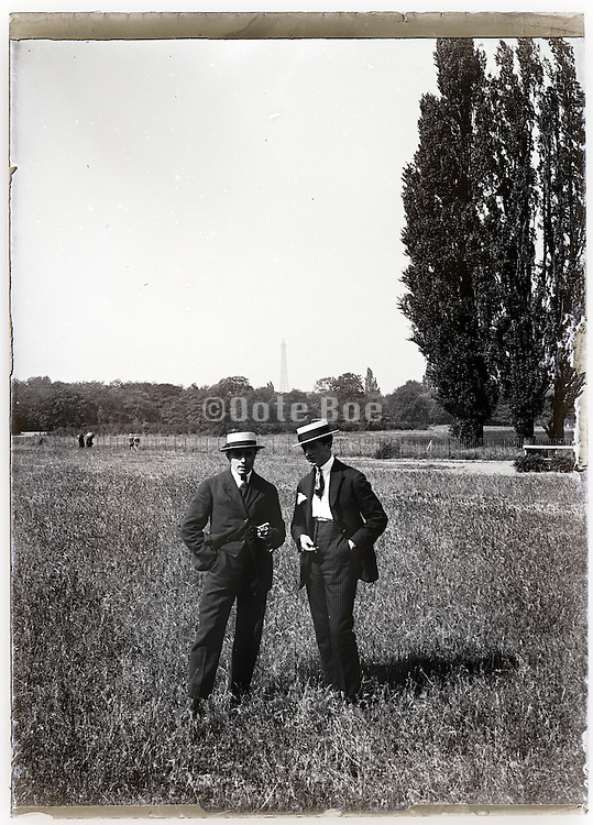 two men in field with Eiffel tower in the background Paris 1900s