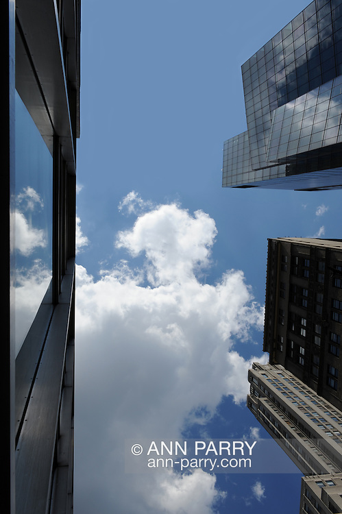 Overhead wide angle view of Manhattan skyline, with reflection of cloudy blue sky reflected in window of nearby skyscraper opposite other skyscrapers