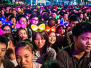 """31 DECEMBER 2012 - BANGKOK, THAILAND:  Thais gather for the New Year's Eve party and countdown in the Ratchaprasong intersection in Bangkok. The traditional Thai New Year is based on the lunar calender and is celebrated in April, but the Gregorian New Year is celebrated throughout the Kingdom, especially in larger cities and tourist centers, like Bangkok, Chiang Mai and Phuket. The Bangkok Countdown 2013 event was called """"Happiness is all Around @ Ratchaprasong."""" All of the streets leading to Ratchaprasong Intersection were closed and the malls in the area stayed open throughout the evening.   PHOTO BY JACK KURTZ"""