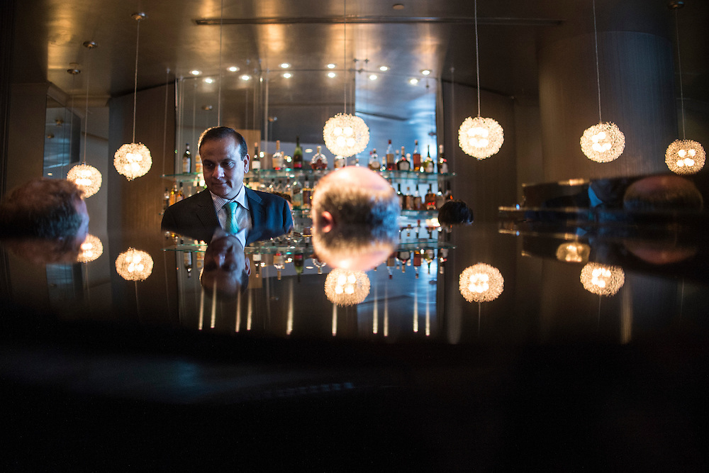 Photo by Matt Roth<br /> Assignment ID: 30142124A<br /> <br /> Restauranteur Ashok Bajaj talks to patrons Brian Wolfe, out of frame, and Robert Aiken, right, in the lounge are of 701, during the nightly rounds of his restaurants in Washington, D.C. on Thursday, May 09, 2013.