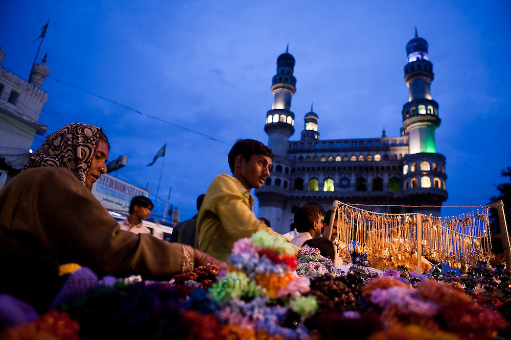 """Shopkeepers and customers deal at a market place adjacent to """"Char Minar"""" monument in Hyderabad, India, on Wednesday July 21, 2010. Photographer: Prashanth Vishwanathan/Bloomberg News"""