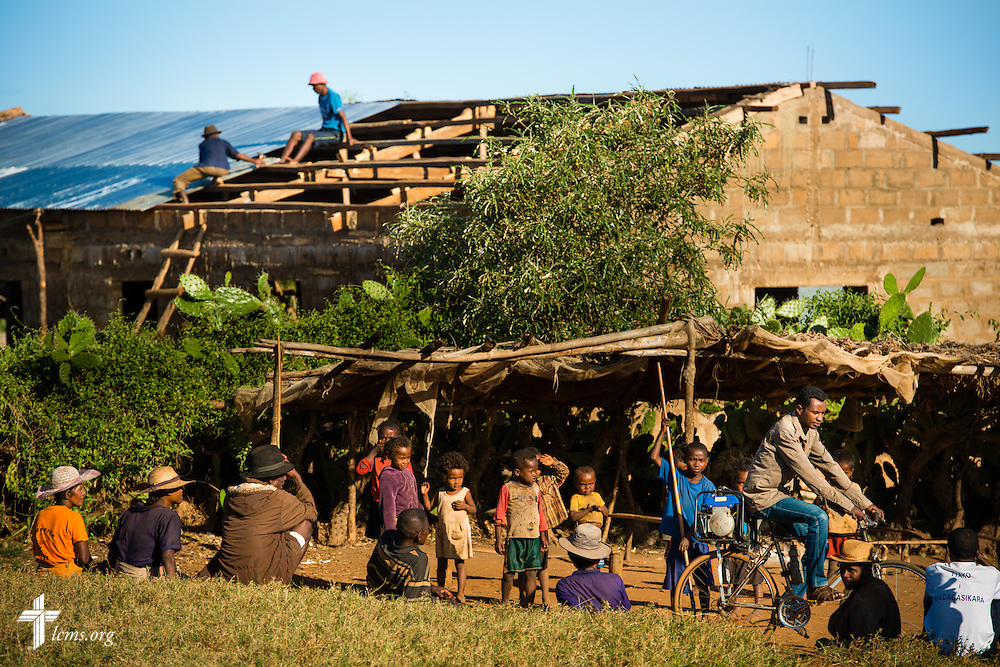 Community members watch as Falesoa Jean-Pierre and Mahavita Arlin install a tin roof onto the Amboasary -1 Fiangonana Loterana Malagasy (FLM, Malagasy Lutheran Church) church near Amboasary, Madagascar, on Wednesday, Oct. 22, 2014. LCMS Communications/Erik M. Lunsford