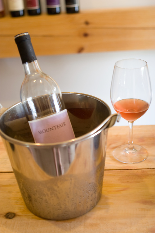 A bottle of Mountfair Vineyards Rose' next to a wine glass, in the Mountfair tasting room.