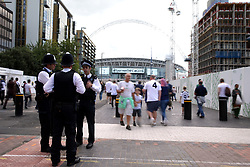 Police presence and fans on Wembley Way ahead of the Premier League match at Wembley Stadium, London.