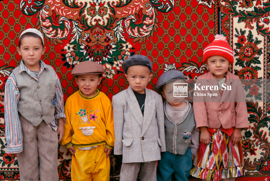 Uighur children in front of a carpet, Kashgar, Xinjiang Province, China