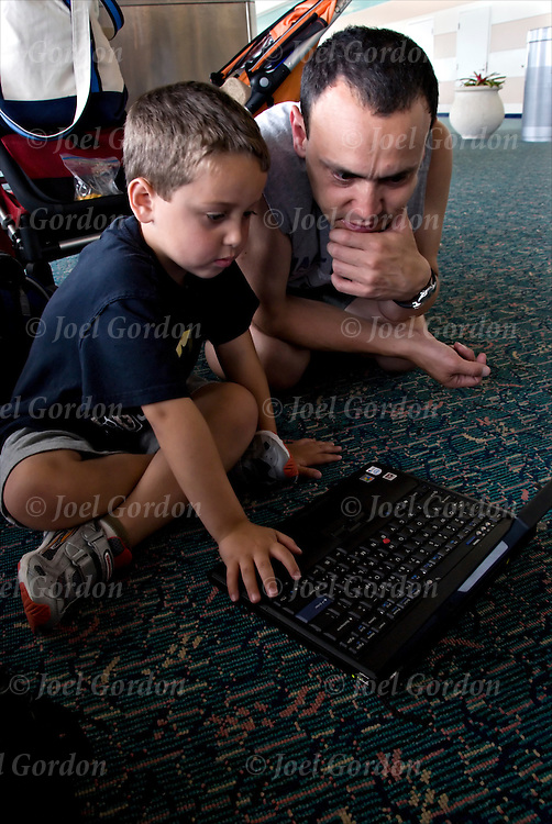 MCO Airport Family Portrait father and son. Flight delayed, father (James, 37) sitting on floor with laptop computer (Francesco, 5) son sitting on this back looking at computer screen.<br /> <br /> release # 2441
