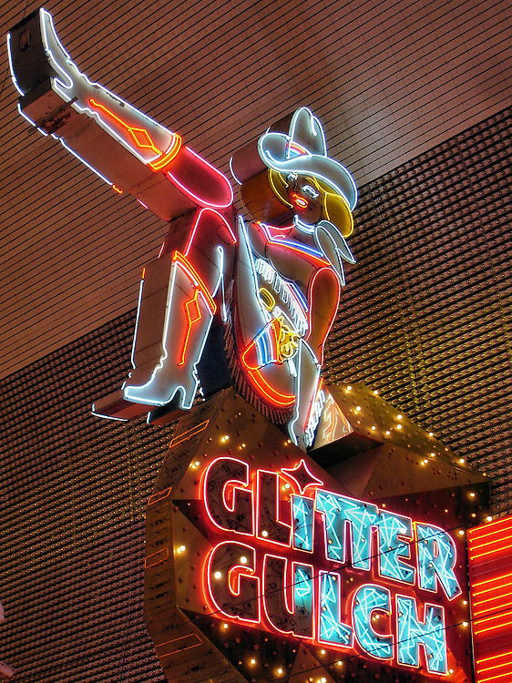 Cowgirl Neon Sign Vegas Vickie in Downtown Las Vegas, Nevada<br /> Las Vegas gambling started on Fremont Street in 1905.  As it grew, the street was nicknamed &ldquo;Glitter Gulch&rdquo; because of its abundance of neon signs.  A strip club borrowed the name to become the Girls of Glitter Gulch and erected this neon sign of a cowgirl kicking up her leg. During a 1994 ceremony, she was married to Vegas Vic, the 40 foot neon cowboy sign across from her at the Freemont Street Experience pedestrian mall.