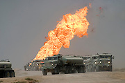 Heading north through the Rumeilah Oil Field of Southern Iraq, convoys of fuel trucks carry the military's mechanical lifeblood past burning oil wells set ablaze by retreating Iraqi forces. (Supporting image from the project Hungry Planet: What the World Eats.)