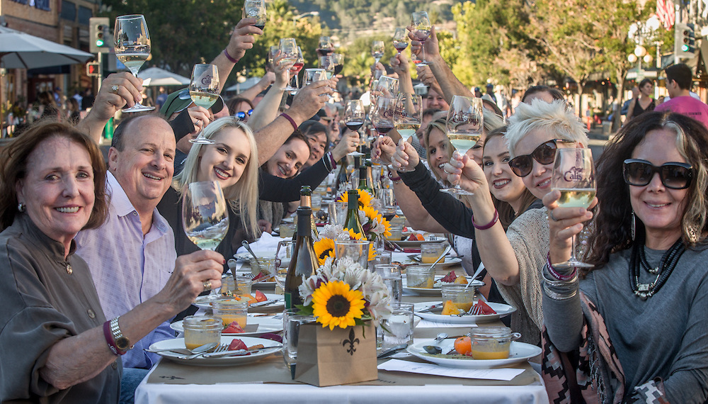 Susan Baxter (far right) and friends toast at the start of annual Harvest Table celebration on Lincoln Avenue in downtown Calistoga, CA