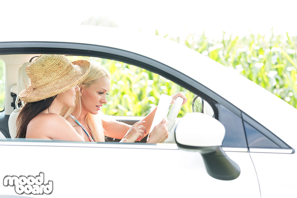 Female friends using digital tablet in car