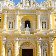 Main entrance of the distinctive  and ornate yellow and white exterior of the Iglesia y Convento de Nuestra Senora de la Merced in downtown Antigua, Guatemala.