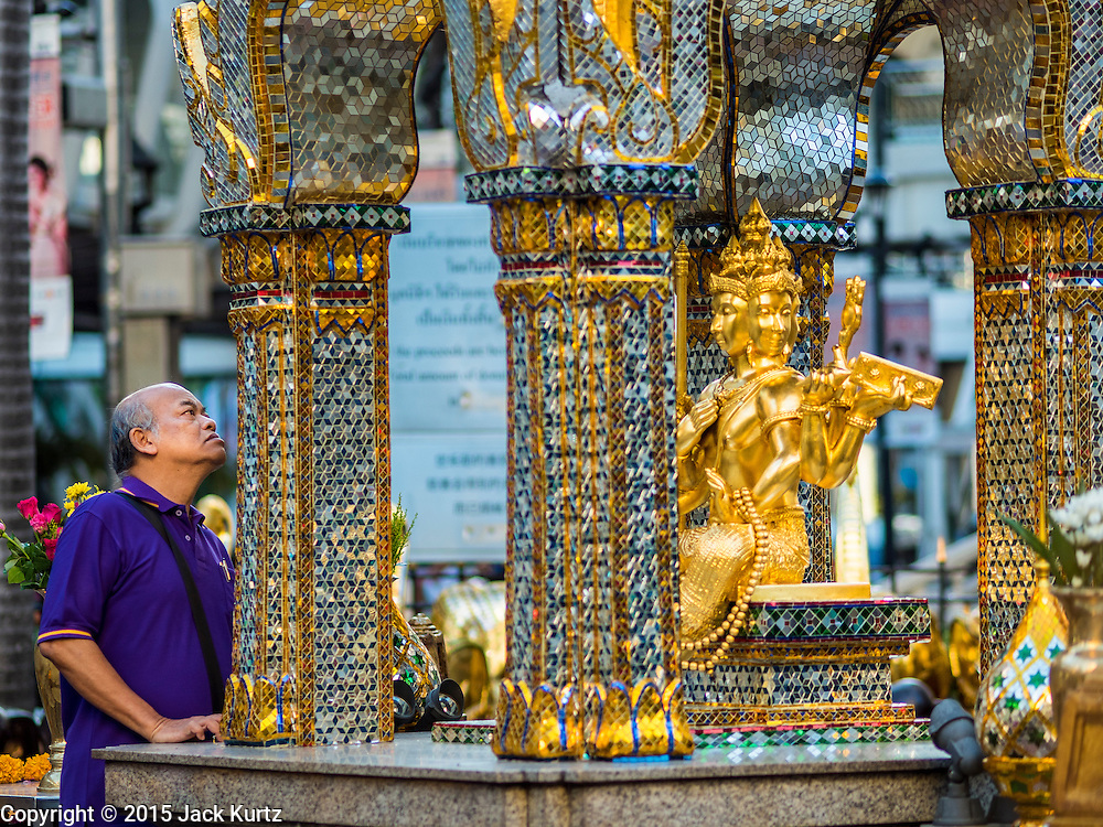 19 AUGUST 2015 - BANGKOK, THAILAND:  A man who works at Erawan Shrine looks at the damaged face on the Four Faced Brahma in the shrine. Erawan Shrine in Bangkok reopened Wednesday morning after more than 20 people were killed and more than 100 injured in a bombing at the shrine Monday, August 17, 2015. The shrine is a popular tourist attraction in the center of Bangkok's high end shopping district and is an important religious site for Thais. No one has claimed responsibility for the bombing.     PHOTO BY JACK KURTZ