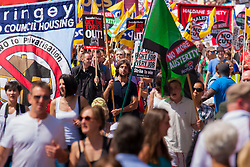 London, June 21st 2014. Flags and banners catch the sun as thousands march against government cuts in London.