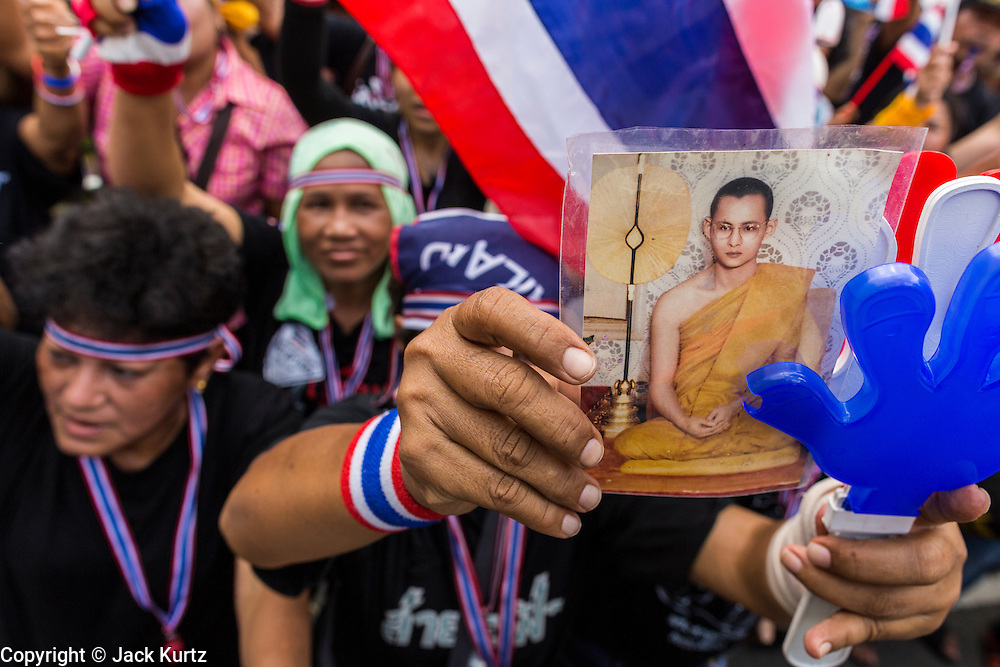 26 NOVEMBER 2013 - BANGKOK, THAILAND: A royalist anti-government protestor holds up a picture of Bhumibol Adulyadej, the King of Thailand, during the protest at the Ministry of Finance. The anti-government protestors are conservative supporters of the monarchy. Protestors opposed to the government of Thai Prime Minister Yingluck Shinawatra spread out through Bangkok this week. Protestors have taken over the Ministry of Finance, Ministry of Sports and Tourism, Ministry of the Interior and other smaller ministries. The protestors are demanding the Prime Minister resign, the Prime Minister said she will not step down. This is the worst political turmoil in Thailand since 2010 when 90 civilians were killed in an army crackdown against Red Shirt protestors. The Pheu Thai party, supported by the Red Shirts, won the 2011 election and now govern. The protestors demanding the Prime Minister step down are related to the Yellow Shirt protestors that closed airports in Thailand in 2008.     PHOTO BY JACK KURTZ