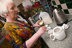 Older woman making a pot of tea,