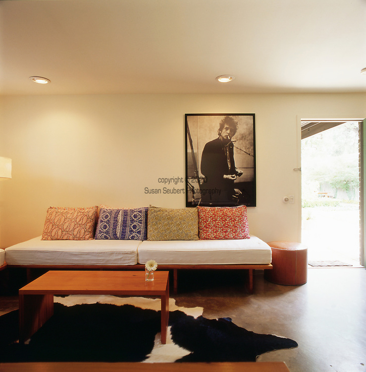 A suite at the Hotel San Jose in Austin, TX features a large photo of Bob Dylan, a cowhide rug and a comfortable seating area.