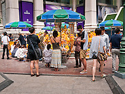 11 JULY 2011 - BANGKOK, THAILAND:  The entrance to the Erawan Shrine in Bangkok. The Erawan Shrine (in Thai San Phra Phrom) is a Hindu shrine in Bangkok, Thailand that houses a statue of Phra Phrom, the Thai representation of the Hindu creation god Brahma. A popular tourist attraction, it often features performances by resident Thai dance troupes, who are hired by worshippers in return for seeing their prayers at the shrine answered. On 21 March 2006, a man vandalised the shrine and was subsequently killed by bystanders. The shrine is located by the Grand Hyatt Erawan Hotel, at the Ratchaprasong intersection of Ratchadamri Road in Pathum Wan district, Bangkok, Thailand. It is near the Bangkok Skytrain's Chitlom Station, which has an elevated walkway overlooking the shrine. The area has many shopping malls nearby, including Gaysorn, CentralWorld and Amarin Plaza. The Erawan Shrine was built in 1956 as part of the government-owned Erawan Hotel to eliminate the bad karma believed caused by laying the foundations on the wrong date..The hotel's construction was delayed by a series of mishaps, including cost overruns, injuries to laborers, and the loss of a shipload of Italian marble intended for the building. Furthermore, the Ratchaprasong Intersection had once been used to put criminals on public display. An astrologer advised building the shrine to counter the negative influences. The Brahma statue was designed and built by the Department of Fine Arts and enshrined on 9 November 1956. The hotel's construction thereafter proceeded without further incident. In 1987, the hotel was demolished and the site used for the Grand Hyatt Erawan Hotel.     PHOTO BY JACK KURTZ
