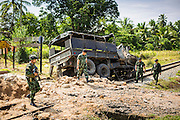 11 JULY 2013 - RAMAN, YALA, THAILAND:  Thai soldiers and their officers walk away from the scene of an IED attack Thursday. Eight soldiers were injured when the IED exploded under a Thai Army truck carrying soldiers back to their camp after they finished a teacher protection mision. The army routinely dispatches soldiers to protect teachers and Buddhist monks, who have been targeted by Muslim insurgents as representatives of the Bangkok government. More than 5,000 people have been killed and over 9,000 hurt in more than 11,000 incidents in Thailand's three southernmost provinces and four districts of Songkhla since the insurgent violence erupted in January 2004, according to Deep South Watch, an independent research organization that monitors violence in Thailand's deep south region that borders Malaysia.   PHOTO BY JACK KURTZ