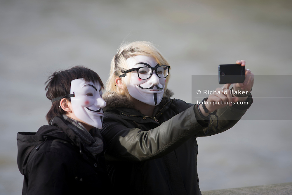 A couple wearing Anonymous masks pose for their own selfie photo.