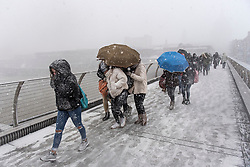 © Licensed to London News Pictures. 27/02/2018. London, UK. Members of the public wade through heavy snowfall on the Millennium Bridge near St Paul's Cathedral in the City of London, as a cold front, named the 'Beast From the East' hits the capital. Amber weather warnings are in place for large parts of the east of the UK as a severe cold front heads in from Russia. Photo credit: Ben Cawthra/LNP