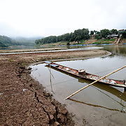 A long, thin wooden boat is moored by bamboo poles in a small sandy bay along the sandy shores of the Nam Ou (River Ou) in Nong Khiaw in northern Laos.