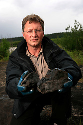 CANADA ALBERTA FORT MCMURRAY 19JUL09 - Greenpeace Germany campaigner Christoph von Lieven holds a piece of bituminous rock at the Bitumount oil extraction site on the river Athabasca north of Fort McMurray, northern Alberta, Canada...jre/Photo by Jiri Rezac / GREENPEACE..© Jiri Rezac 2009