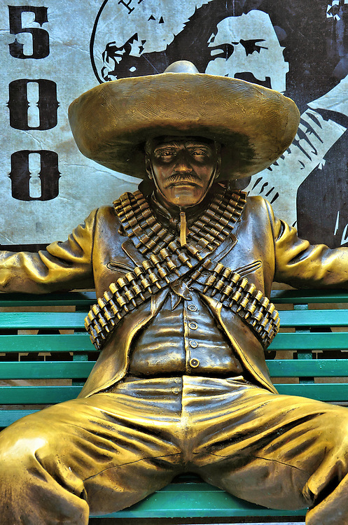 Mexican Bandito Statue in Playa del Carmen, Mexico<br /> The origin for the stereotypical Mexican bandito was probably General Pancho Villa, a 20th century revolutionary hero.  He often wore crisscrossed bandoliers across his chest. Then movies embellished the appearance of outlaws with the sombrero, thick mustache and nasty sneer. Even Frito Corn Chips immortalized the look during their advertisements from 1967 through 1971 featuring the cartoon character Frito Bandito.  This bronze statue on a bench along La Quinta Avenida makes a perfect photo op of your Mexican vacation.