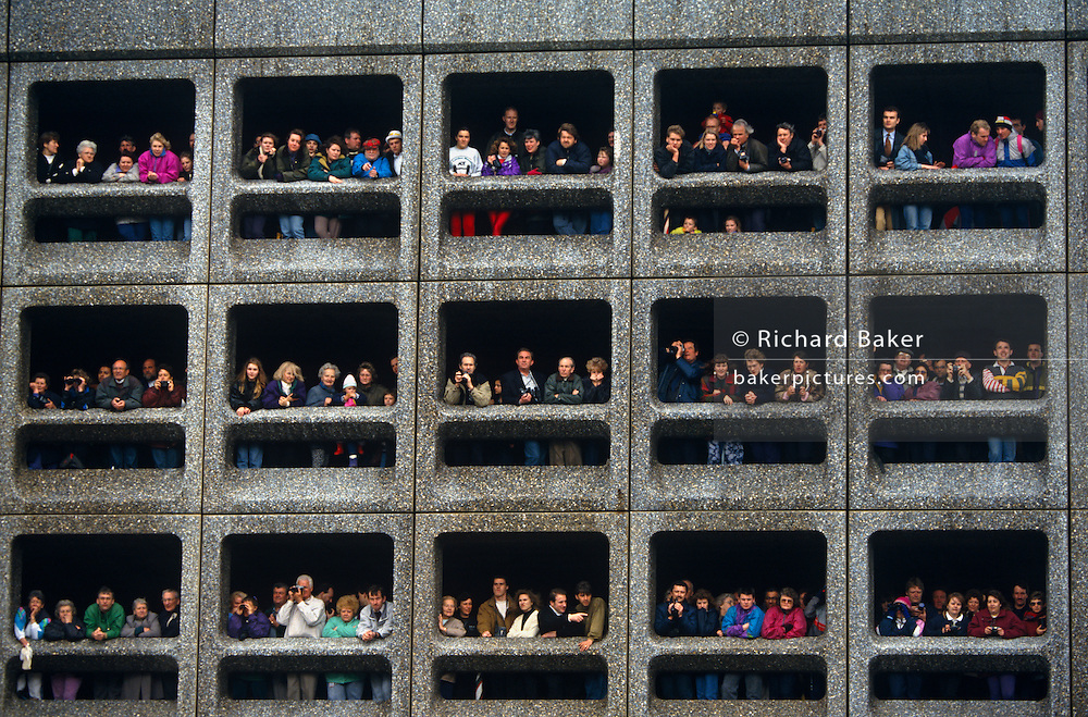 We are looking up from the ground to crowds gathered in three levels of a multi-story car park to await athletes pass during the London Marathon. The runners will make their way through the streets of East London beneath these spectators who have been patiently waiting for their friends and families to pass below. It is a great viewpoint from which to view such a sporting spectacle and we are peering up at the supporters leaning against the discoloured (discolored) concrete architecture dating back to the 1970s. It is the best elevated place to witness the race. There are three rows of 5 columns totalling 15 seperate windows and each one is full of families young and old. They resemble the compartments of a garden pet hutch where rabbits are kept in cramped conditions.
