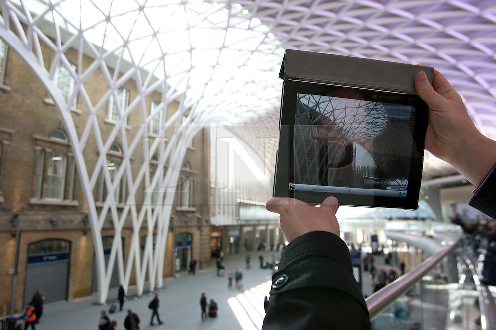 © licensed to London News Pictures. London, UK 19/03/2012. A person using their iPad to take a picture of the new concourse at King's Cross train station in London which opened to commuters today (19/03/2012). Photo credit: Tolga Akmen/LNP