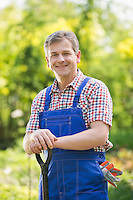 Portrait of happy gardener holding spade in plant nursery