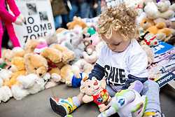 © Licensed to London News Pictures. 22/10/2016. London, UK. A young child plays with a teddy outside Downing Street, as activists take part in the 'Rally For Aleppo', calling for the government to do more to stop the bombing in Syria. Photo credit : Tom Nicholson/LNP