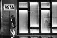 Young woman using a cell phone in front of the Hugo Boss store at the Time-Warner Center on Columbus Circle
